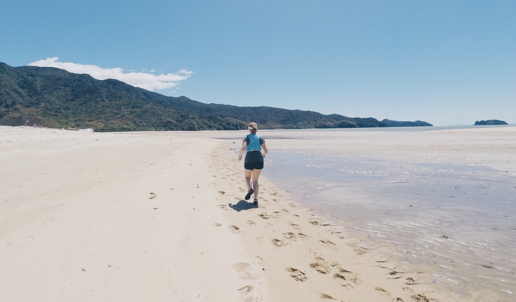 Helen running along a beach in Abel Tasman